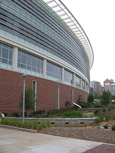 A segment of a curved building constructed from brick, metal and glass