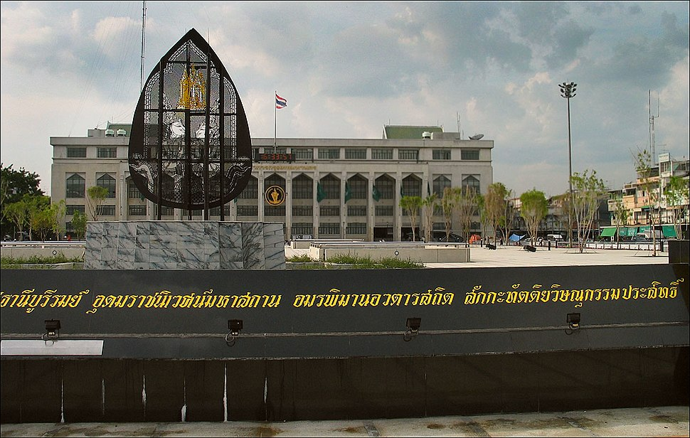 A granite sign with a long name in Thai script, and a building in the background