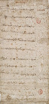 Long vertical mottled grey paper, with a dozen widely spaced lines of horizontal Arabic-looking script. There are two small oval red designs which have been stamped along the righthand margin of the paper.