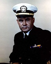 A man in a dark suit and tie, with a white peaked cap. Hears wears the two gold stripes of a lieutenant on his sleeve, and ribbons including those of the Distinguished Service Cross and Silver Star.