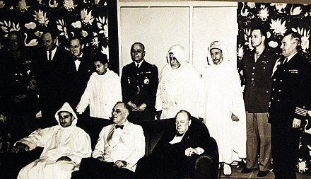 Prince Hassan at 13 years old, third from left in back row, photographed behind Sultan Muhammad V, President Franklin D. Roosevelt, and Prime Minister Winston Churchill during the Casablanca Conference of 1943. Lot 11568-2 (24632562862).jpg