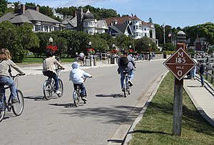Mackinac Island - Cyclists on M-185 (Main Street) at mile marker 0 in downtown Mackinac Island