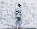 Man leans against gray wall (Unsplash).jpg
