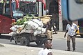Man pulling a cart packed with goods on a busy Mombasa streets.jpg