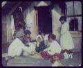 Maori woman and children playing cards on doorstep of home - Whakarewarewa LCCN2004707876.tif