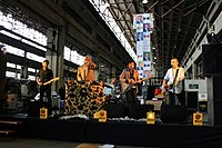 Four males standing at microphones with three playing guitars, second male from left at keyboards, all are inside an industrial shed with skylights behind.