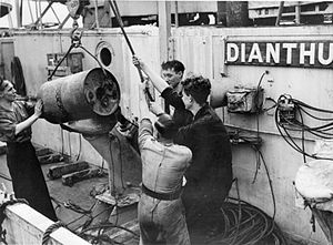 Convoy SC 121 - A depth charge being loaded onto a depth-charge thrower aboard the corvette HMS Dianthus