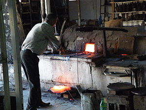 Hebron glass - Carefully moving molten glass as part of the modern production process