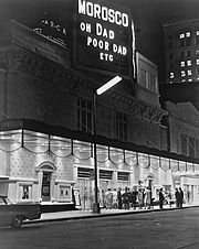 Night. Plain-looking theatre front from across the street, at an angle. Under the marquee, which is as wide as the theatre, a dozen or so people standing in front of the entrance are in bright light. Atop the building, a large sign announces the theatre's name and the play's name (abbreviated as Oh Dad Poor Dad, etc.). Everything else above the marquee, including nearby and distant buildings, is in relative darkness, but the street lights and illuminated signs and windows make it  visible.