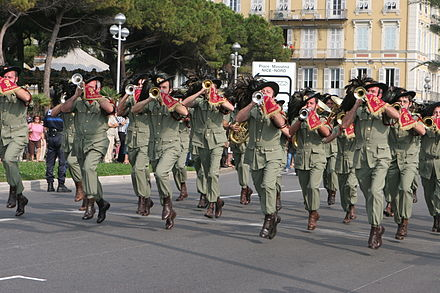 An Italian Bersaglieri fanfare band. As they lack percussion instruments, the band marches at a jogging pace. Musique Bersaglieri 01.JPG