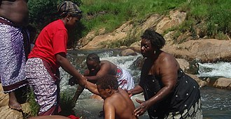 Tsonga people - Senior N'angas help a new n'agna out of the water during an initiation