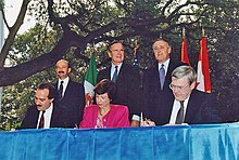 Two men and one women sit at a table and sign a piece of paper, while three men in suits stand behind them, in front of a set of limp flags