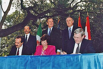NAFTA signing ceremony, October 1992. From left to right: (standing) President Carlos Salinas de Gortari (Mexico), President George H. W. Bush (U.S.), and Prime Minister Brian Mulroney (Canada) Nafta.jpg