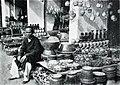 Người đàn ông bán đồ gốm bên quầy hàng, năm 1900.jpg