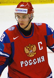 A young man wearing a red helmet and red jersey with a stylized eagle and Cyrillic writing on the front.