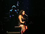 Woman in black sleeveless top and multicolored skirt sitting at a piano in a performance hall with a band behind her.