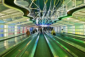"Transportation in Chicago - Michael Hayden's neon installation ""Sky's the Limit"" (1987) in a subterranean walkway at O'Hare Airport. Sometimes called ""The Gershwin Tunnel"", the walkway connects concourses B and C of Terminal 1, which is operated by United Airlines."