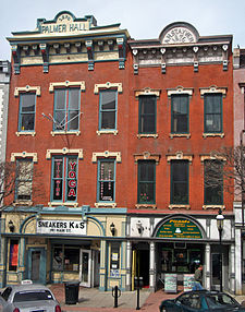 "Two attached brick buildings three stories height with colorful, ornate detailing and storefronts at street level. The one on the left has ""Sneakers K & S"" on its storefront and ""Palmer Hall"" at the top. The one on the right has ""Picante"" at the storefront and ""A.H. Stayver 1876"" at the top."