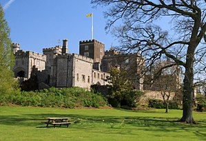 Powderham Castle - Powderham Castle seen from the south west, flying the heraldic flag of the Earl of Devon