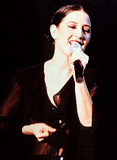 Sepiatone image of Donna De Lory singing with a microphone in her left hand.
