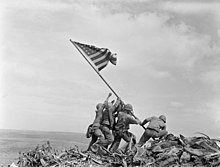 Four soldiers plant a U.S. flag on a long pole on a bare mountaintop