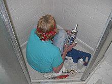 Repairing Damaged Tile In A Shower Stall With Caulking Gun