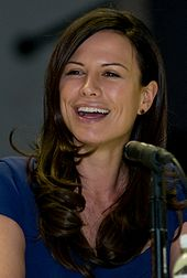 A seated woman with brown hair extending below her shoulders and wearing a blue shirt smiles as she looks to her right.