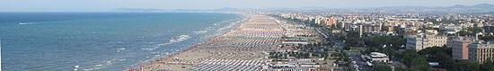 Veduta panoramica della spiaggia di Rimini, dominata sullo sfondo dalle colline romagnole e dal promontorio di Gabicce