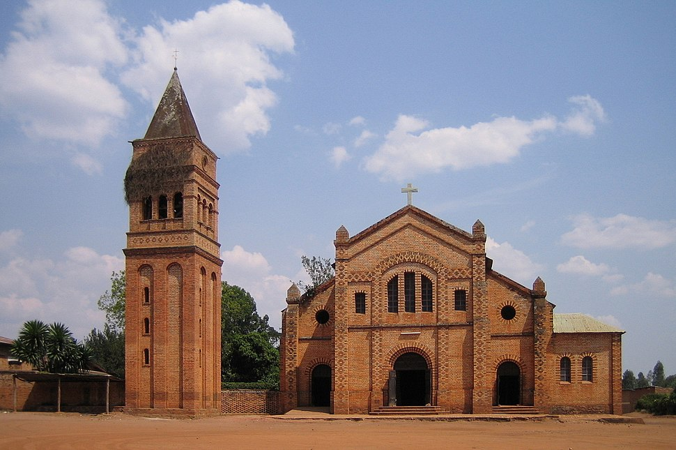 Photograph depicting the Roman Catholic parish church in Rwamagana, Eastern Province, including the main entrance, façade, the separate bell tower, and dirt forecourt