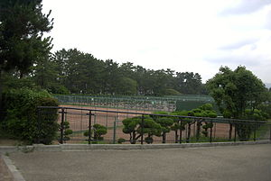 Hattori Ryokuchi Park - Tennis courts in the park, surrounded by sculpted trees.
