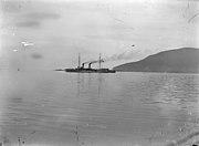 A long, slender ship with a tall smoke stack belching thick black smoke.