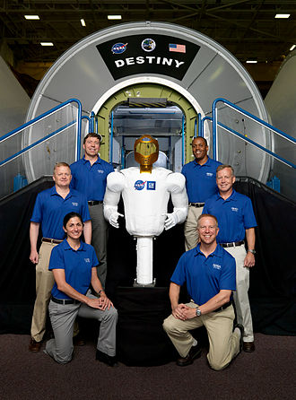 STS-133 - Robonaut2 and STS-133 crew members pose for a picture near a Destiny lab trainer. (Photo includes original crew member Tim Kopra, who was later replaced by Stephen Bowen)
