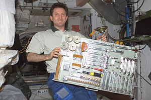 Sergei Treshchov - Sergei Treshchov holds a pallet containing various tools in the ''Unity'' node on the ISS.