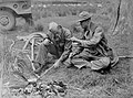 Serviceman lighting cigarette from a frond held by another serviceman (AM 85194-1).jpg