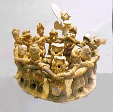 A ring of twelve dancing figures, arms interlocked around each other's shoulders. They surround one musician in the centre of the ring, and a second musician stands behind them.