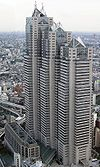 Aerial view of a building's two beige facades with horizontal rows of windows set in front of a cityscape; the building is composed of three adjoined towers of differing heights, each capped off with triangular glass structures