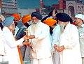 Shri Prakash Singh Badal honouring the Prime Minister Dr. Manmohan Singh by presented a 'Siropa' to him at 'Prakash Utsav' to celebrate the quadricentennial celebration of the installation of Shri Guru Granth Sahib at Golden.jpg