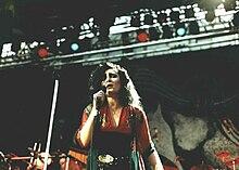 Une femme au teint blanchâtre et aux yeux très maquillés de noir, avec d'épais cheveux noirs ébouriffés, chante sur scène en tenant un micro.