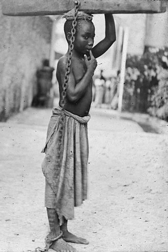 History of slavery in the Muslim world - A photograph of a slave boy in the Sultanate of Zanzibar. 'An Arab master's punishment for a slight offence.' c. 1890