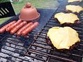 Smoked burgers and hotdogs flaming on the bbq grill.jpg