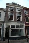 foto van Pand van twee bouwlagen met steil zadeldak met wolfseinden, de nok loodrecht op de straat