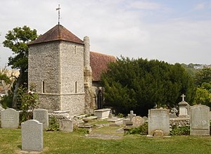 St Wulfran's Church, Ovingdean - View across the churchyard from the southwest, showing the yew tree by the entrance door