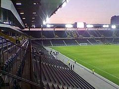 Vue d'un stade de football depuis les tribunes à la tombée de la nuit, les sièges forment les lettres « YB »