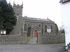 Gray bstone building with square tower to the left hand end, partially obscured by tree. In the foreground is a stone wall separating the church from the road.