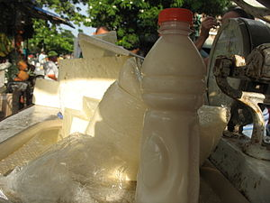 Suero - A bottle of suero costeño in foreground and costeño cheese in background at a market stand in Barranquilla