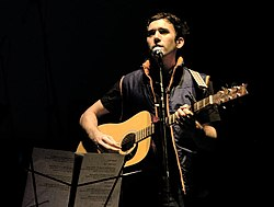 Sufjan Stevens plays guitar in front of a music stand and sings into a microphone