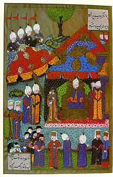 A woman holding a baby in her arms stands before a man who wears a turban and sits on a throne in a tent which is surrounded by dozens of people