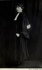 A full-length, black and white photograph of a woman wearing judicial robes