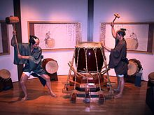 A display at the Osaka Human Rights Museum depicting two workers, wielding large mallets, in the process of applying appropriate tension to a taiko.