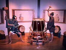 Ekrano ĉe la Osaka Homaj Rajtoj-Muzeo prezentanta du laboristojn, uzante grandajn maleojn, en la procezo de aplikado de konvena streĉiteco al Taiko.